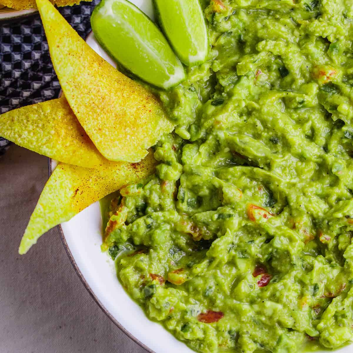 green guacamole in white bowl with lime and tortilla chips