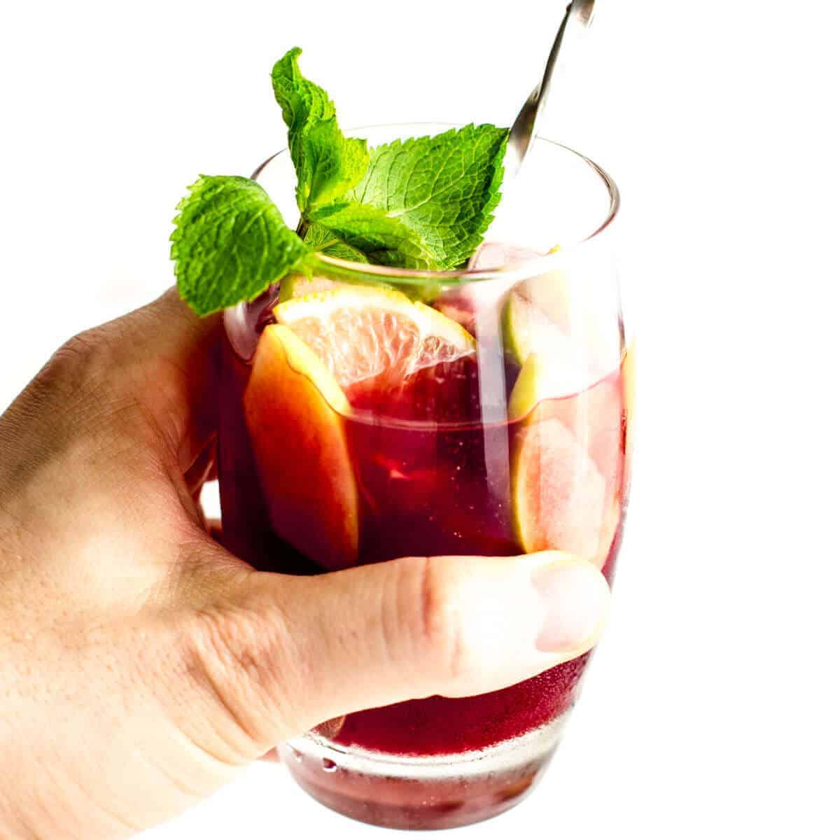 hand holding a glass of red sangria with mint, lemon, apples and ice