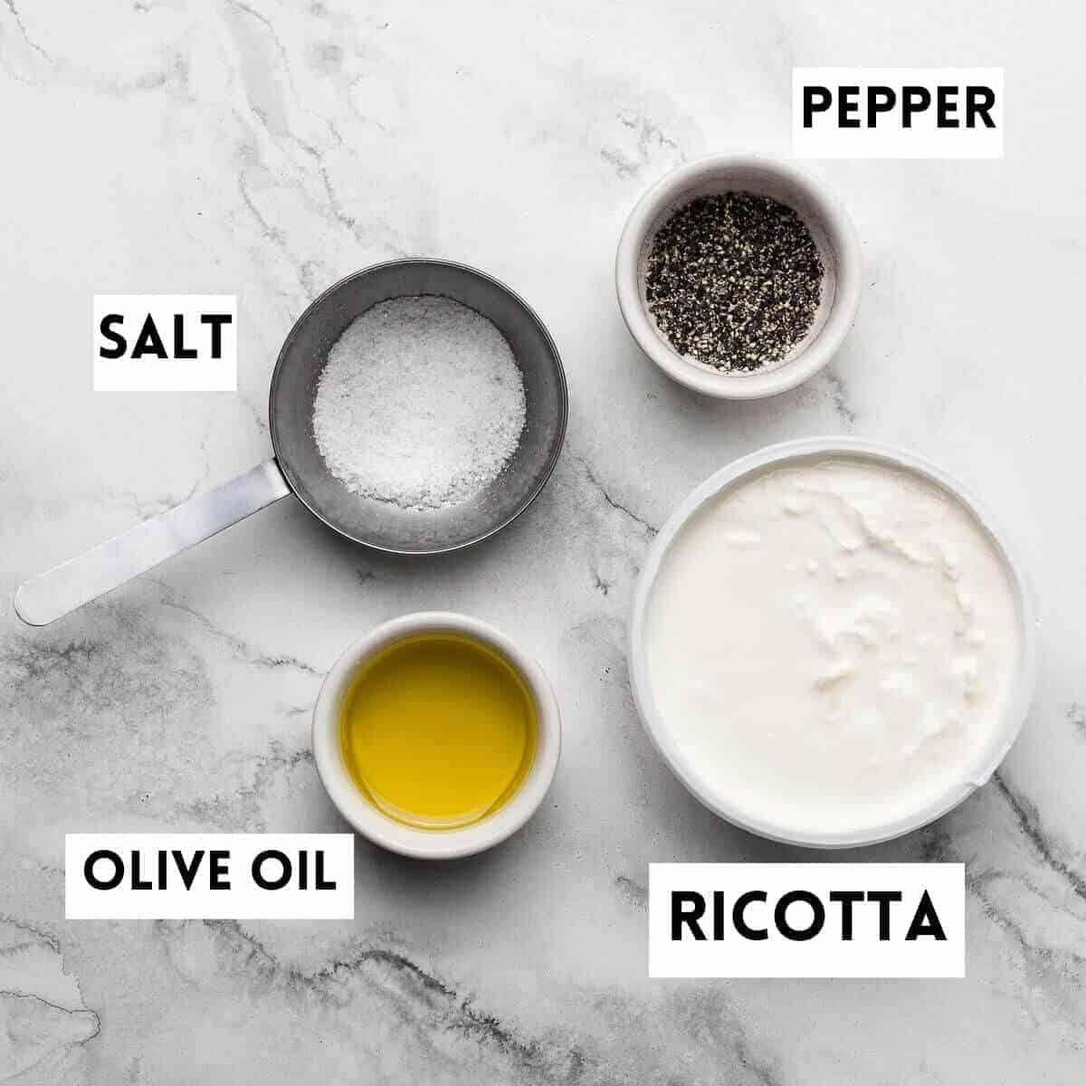 olive oil,salt,pepper and ricotta on marble background