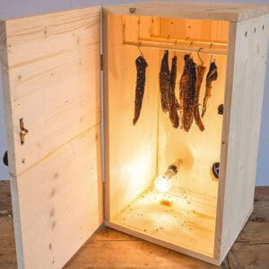 wooden box with meat hanging and light burning