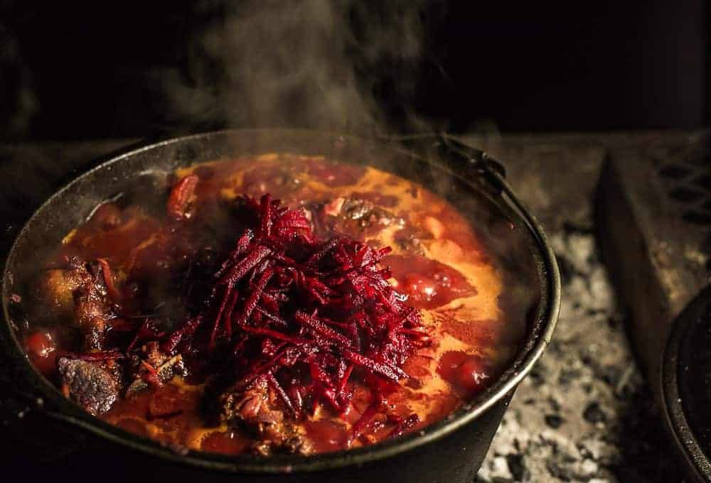 borscht cooking over the fire in a cast iron potjie