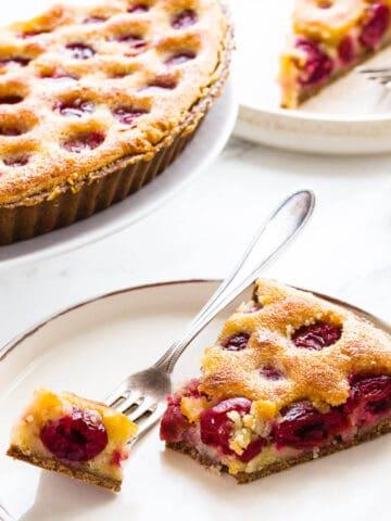 cherry tart slice on white plate with fork.