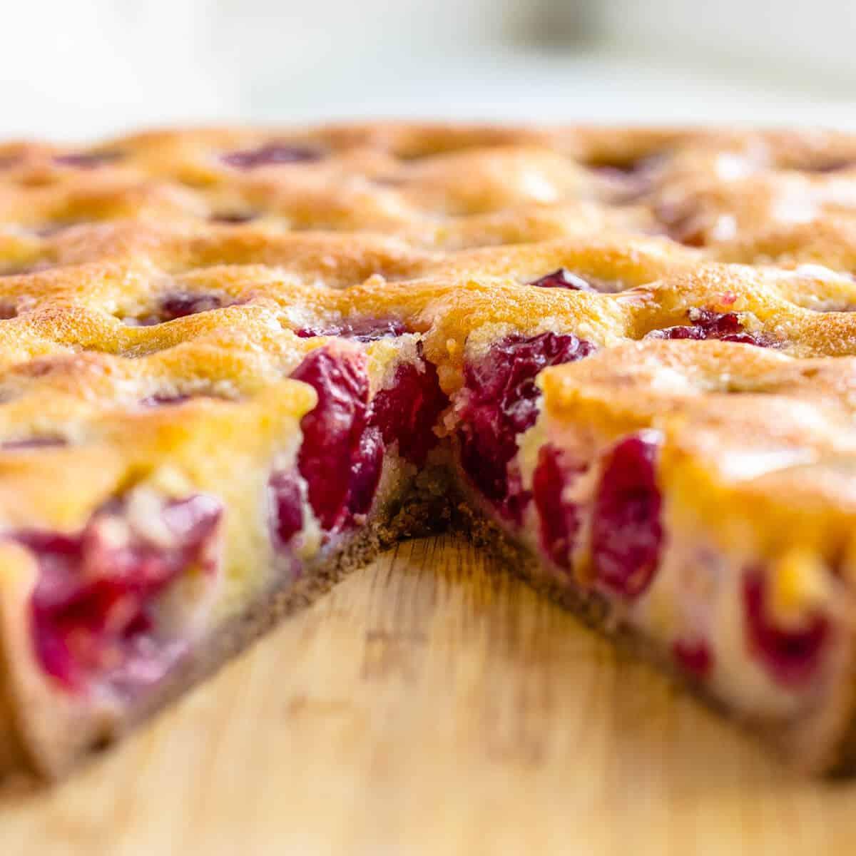 cross section of cherry tart on wooden board.