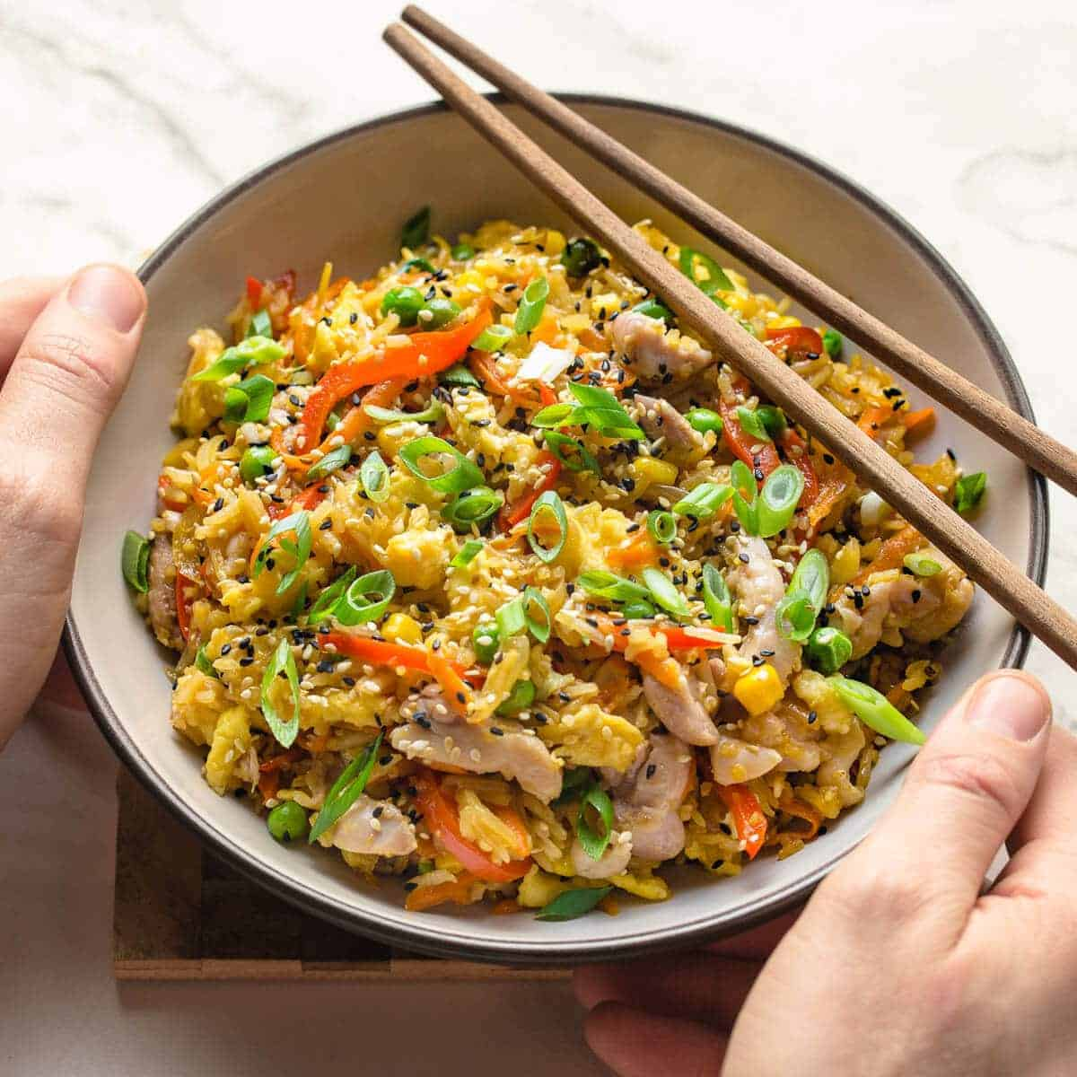 chicken fried rice in a bowl with chopsticks
