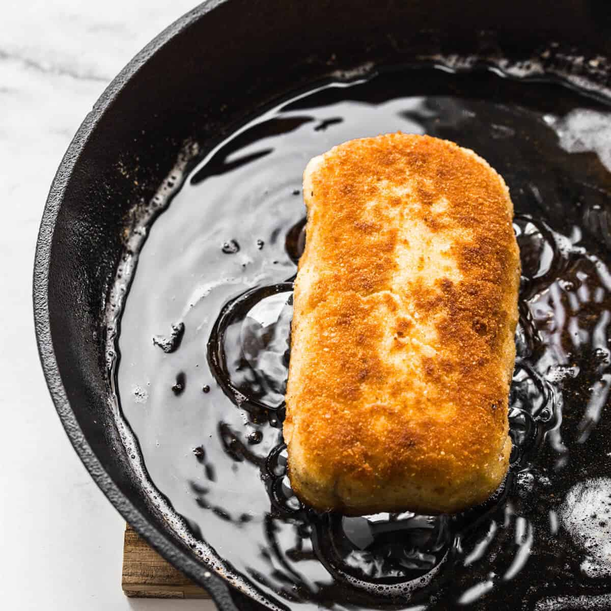 chicken kiev frying in oil in a black skillet