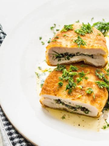 chicken kiev with mashed potatoes and dill on a white plate