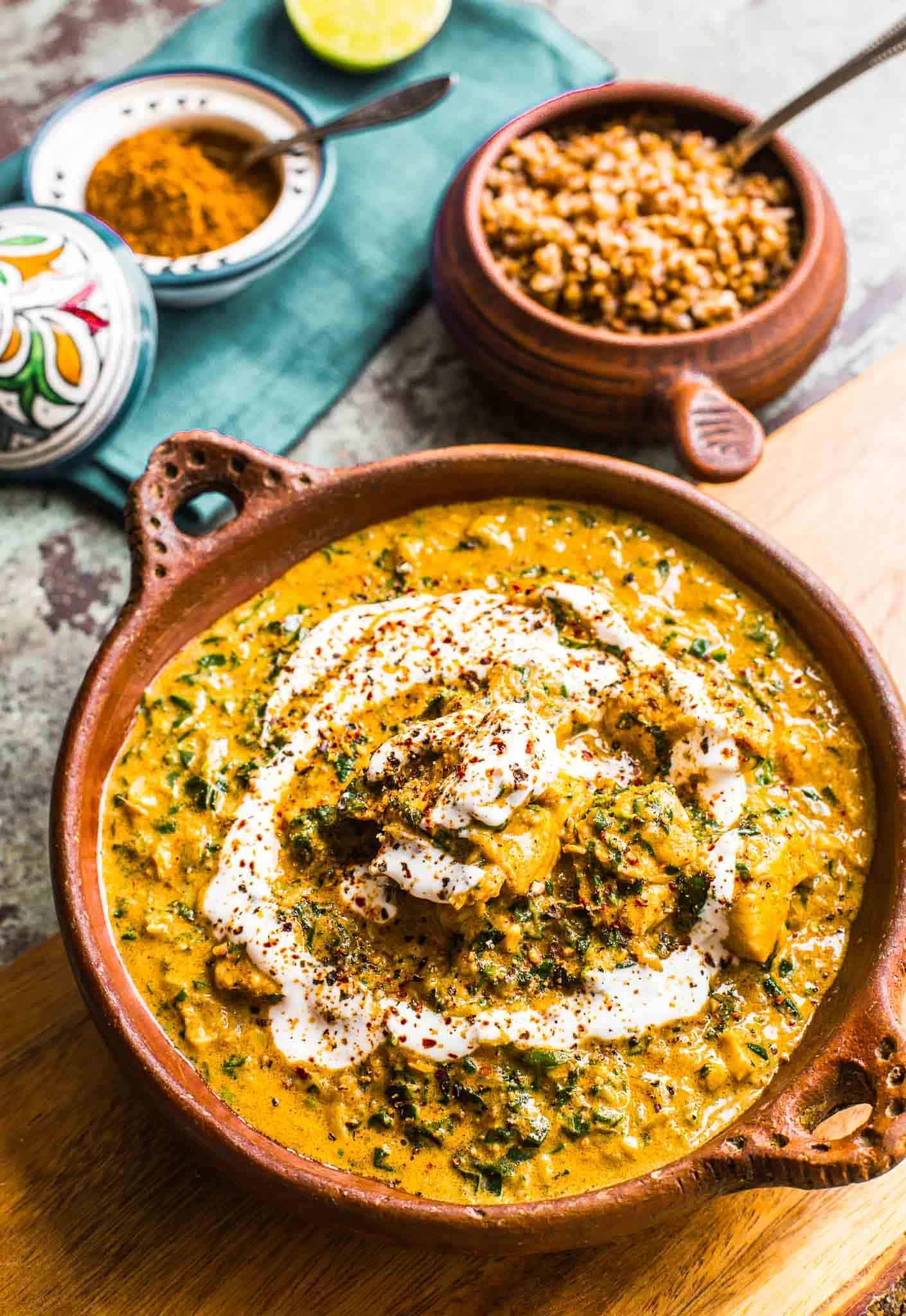 yellow creamy coconut curry on brown bowl on wooden board