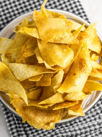corn tortilla chips on a beige plate and black checkered napkin