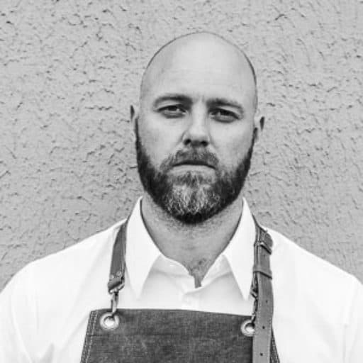 black and white picture of chef standing against wall