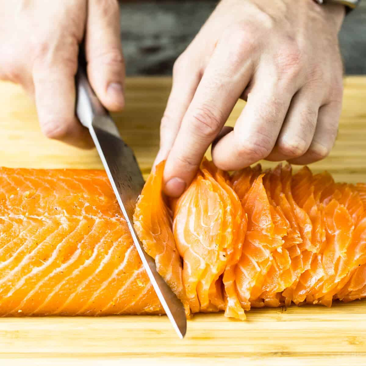slicing cured salmon gravlax on a wooden board