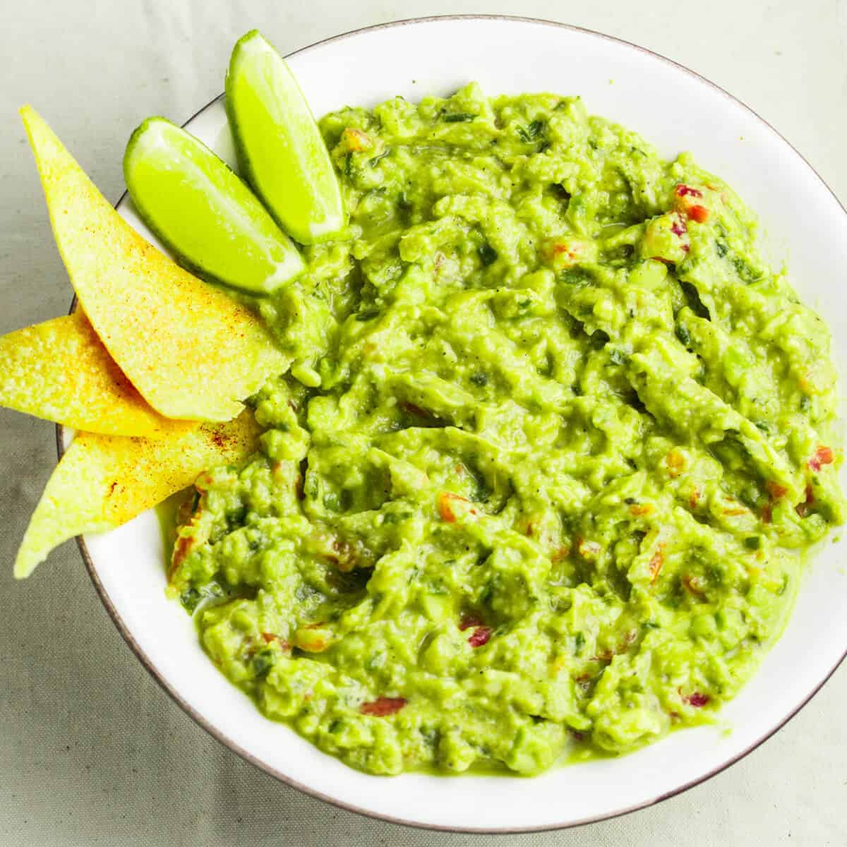 guacamole in white bowl with tortilla chips