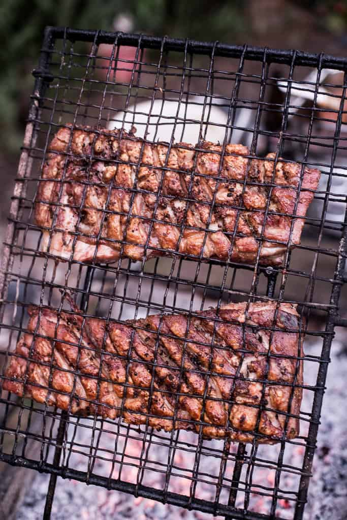 crispy pork belly on black grill over hot embers