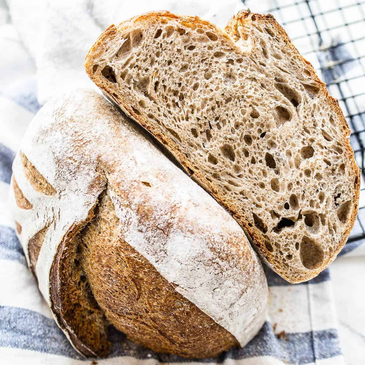 flaxseed meal sourdough bread cut in half on striped kitchen towel
