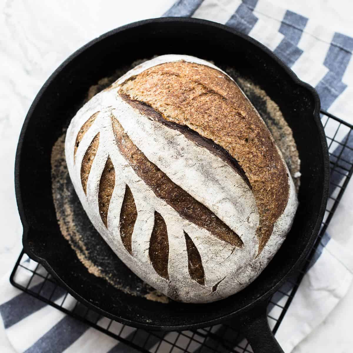 flaxseed meal sourdough in a black skillet on a wire rack and blue and white striped kitchen towel