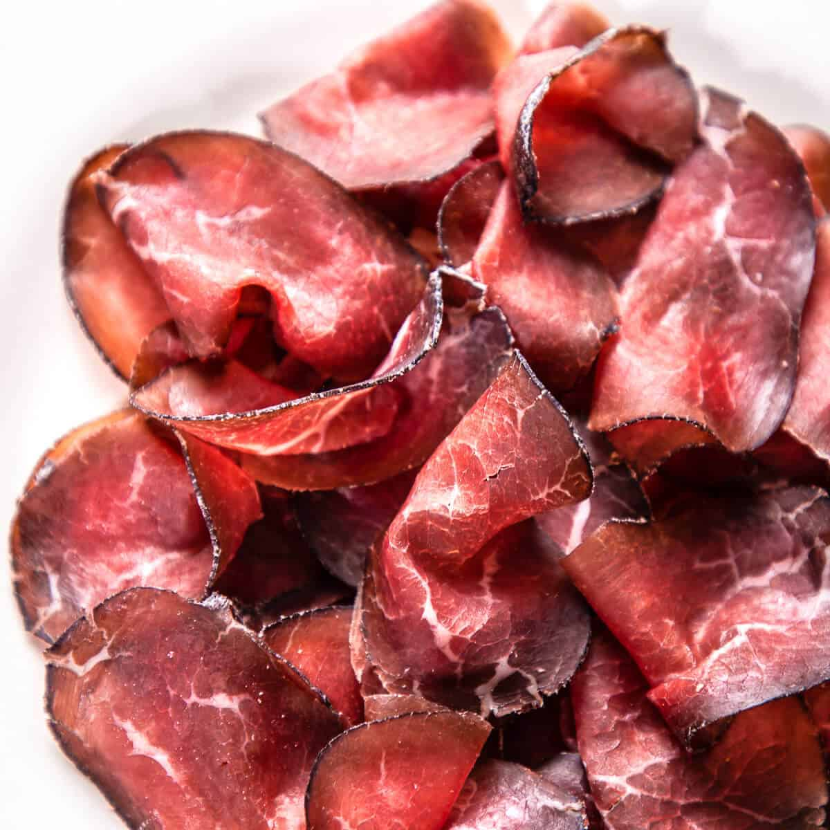 sliced cured beef bresaola on white plate