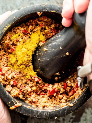 pounding massaman curry paste in black pestle and mortar.
