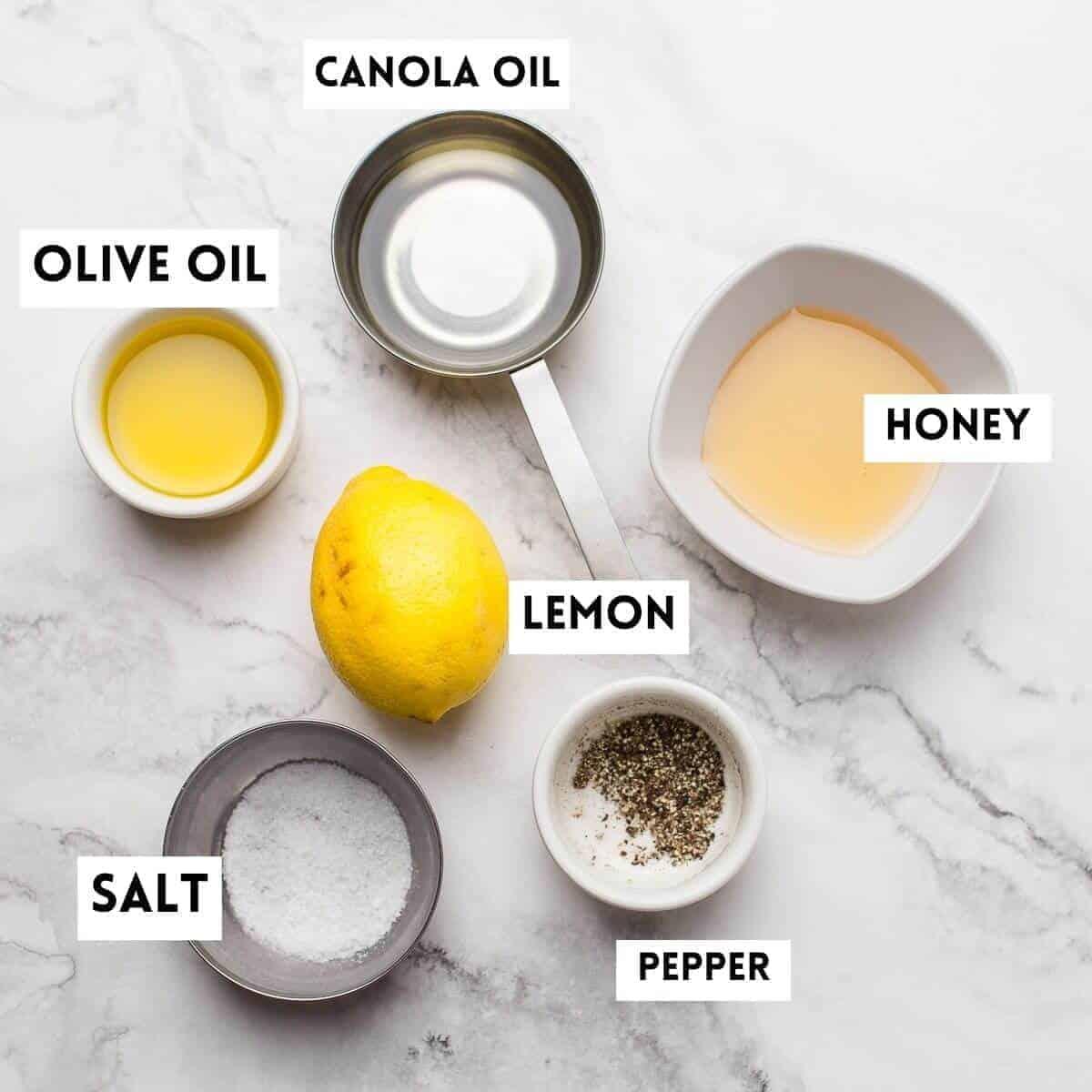 ingredients to make honey lemon dressing. hoey,lemon, olive oil,salt,pepper,canola oil on marble background