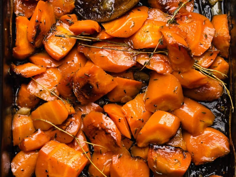 hooney roasted orange carrots with thyme leaves in black oven tray