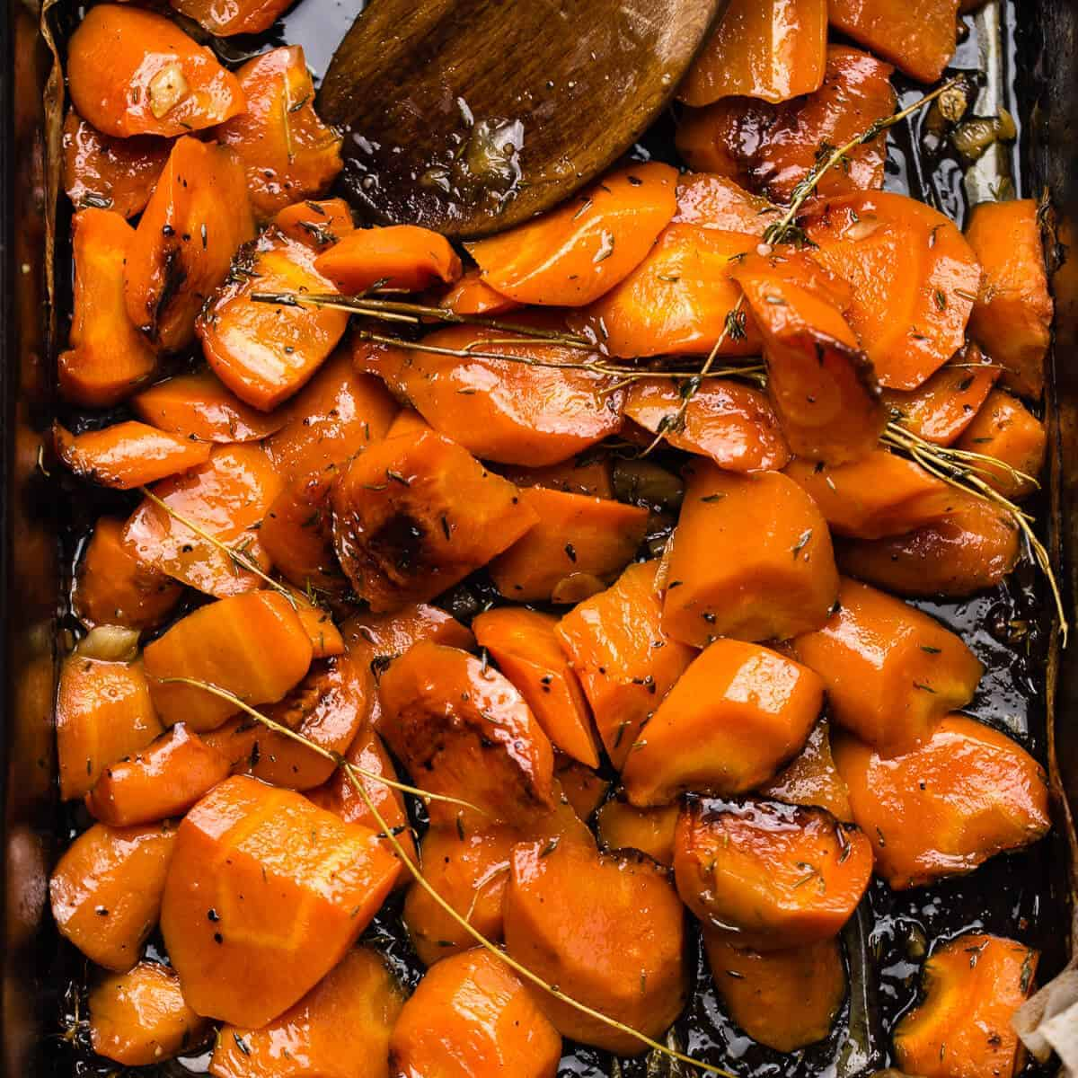 honey roasted orange carrots with thyme leaves in black oven tray