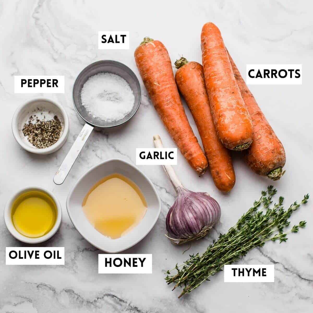 ingredients needed on marble. carrots,honey,garlic,thyme,salt,oil,pepper
