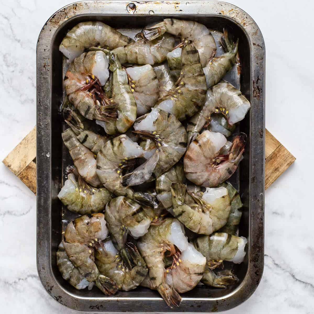 headless raw shrimps on a metal tray on a wooden coaster and marble background