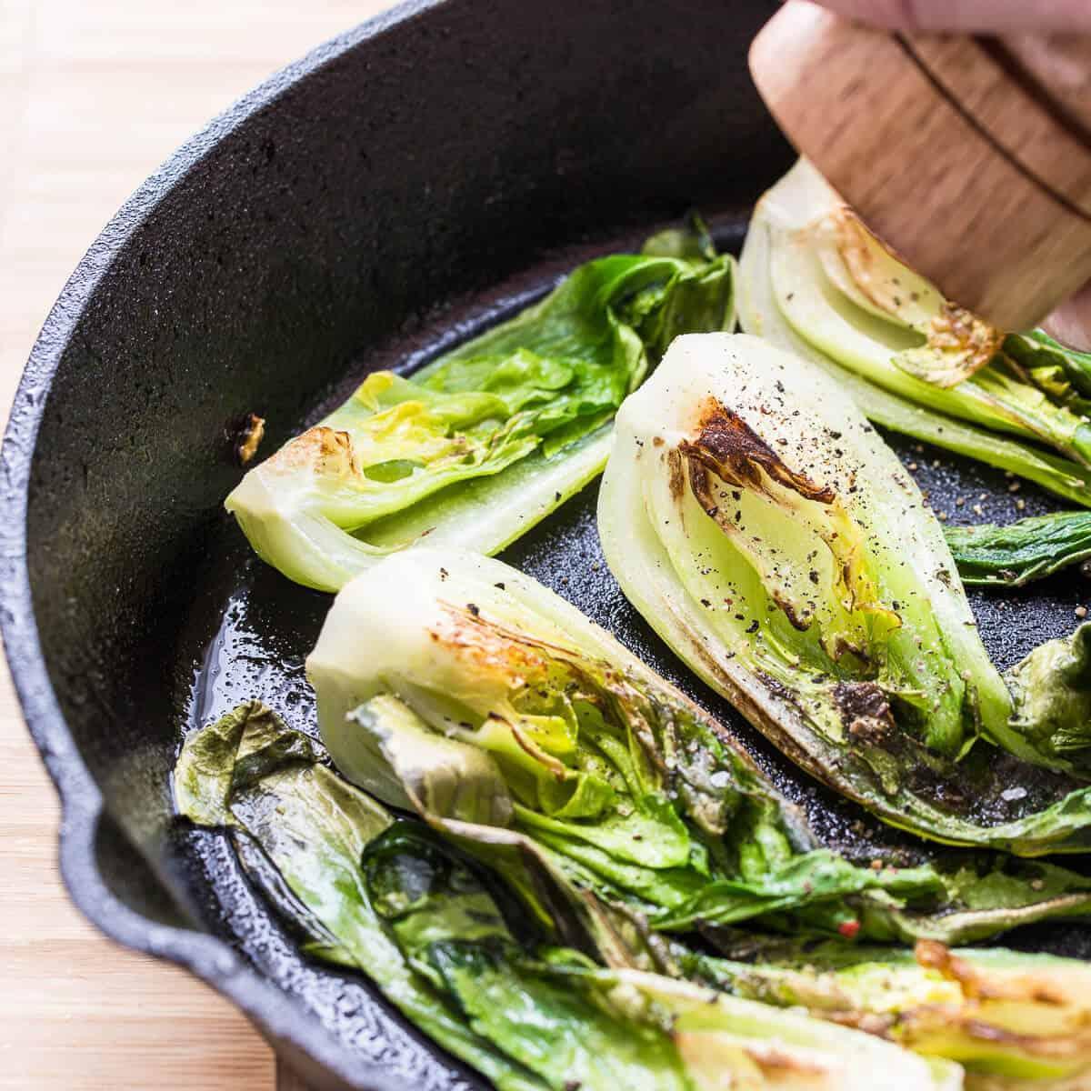 seasoning stir fry bok choy in skillet with pepper.