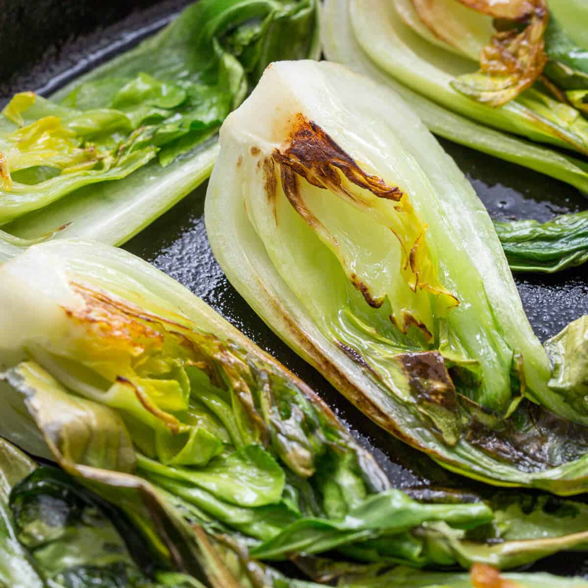 bok choi cooking in a black cast iron skillet.