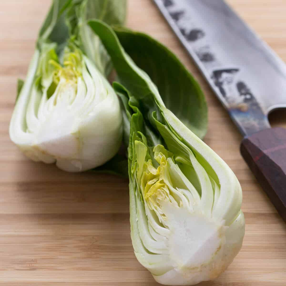 cut bok choy on wooden board next to a knife.