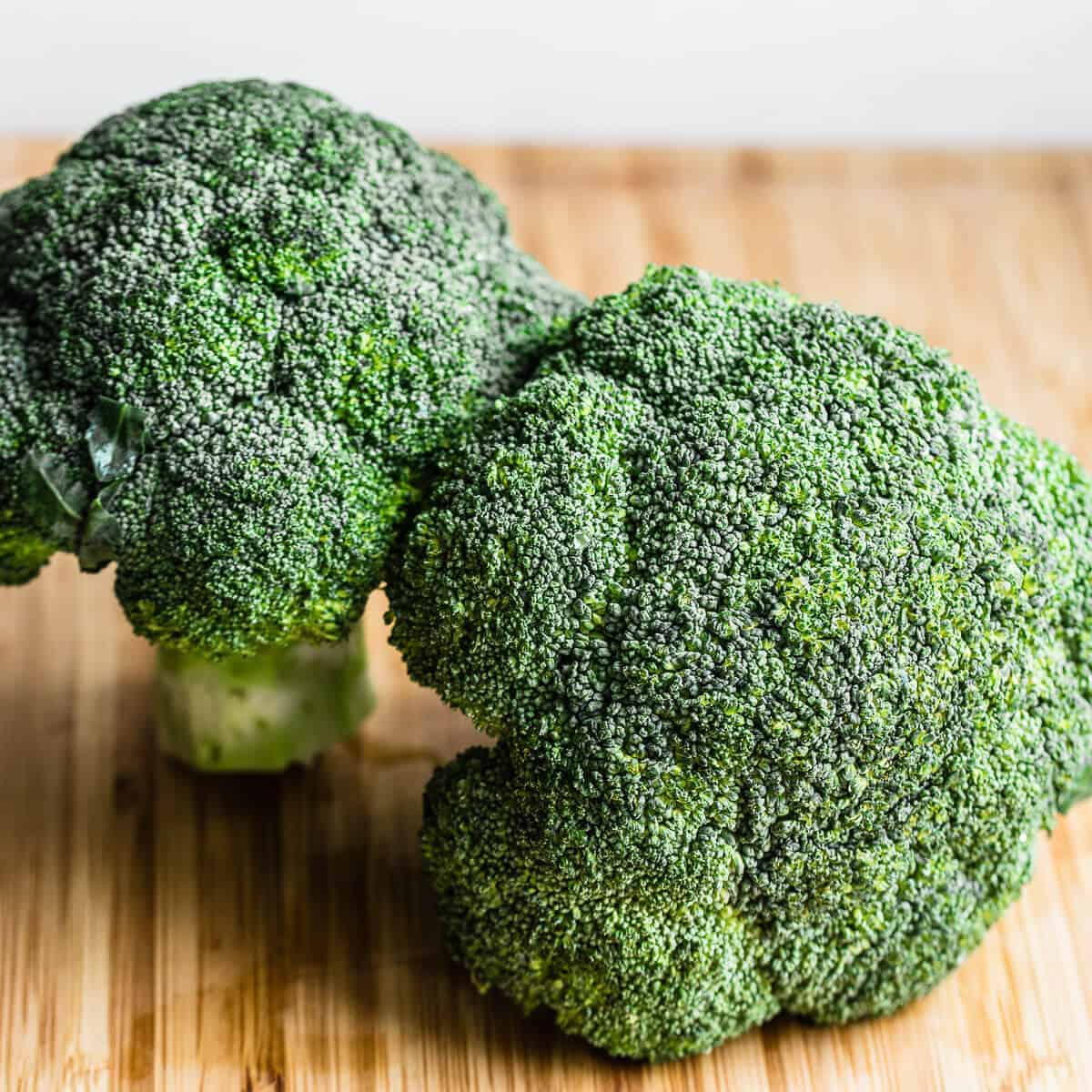 two heads of broccoli on wooden board