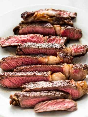 medium rare ribeye steak cooked in a cast iron skillet sliced on a white plate