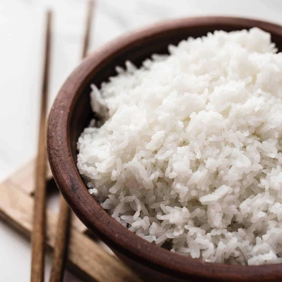 white steamed rice in brown bowl with chopsticks