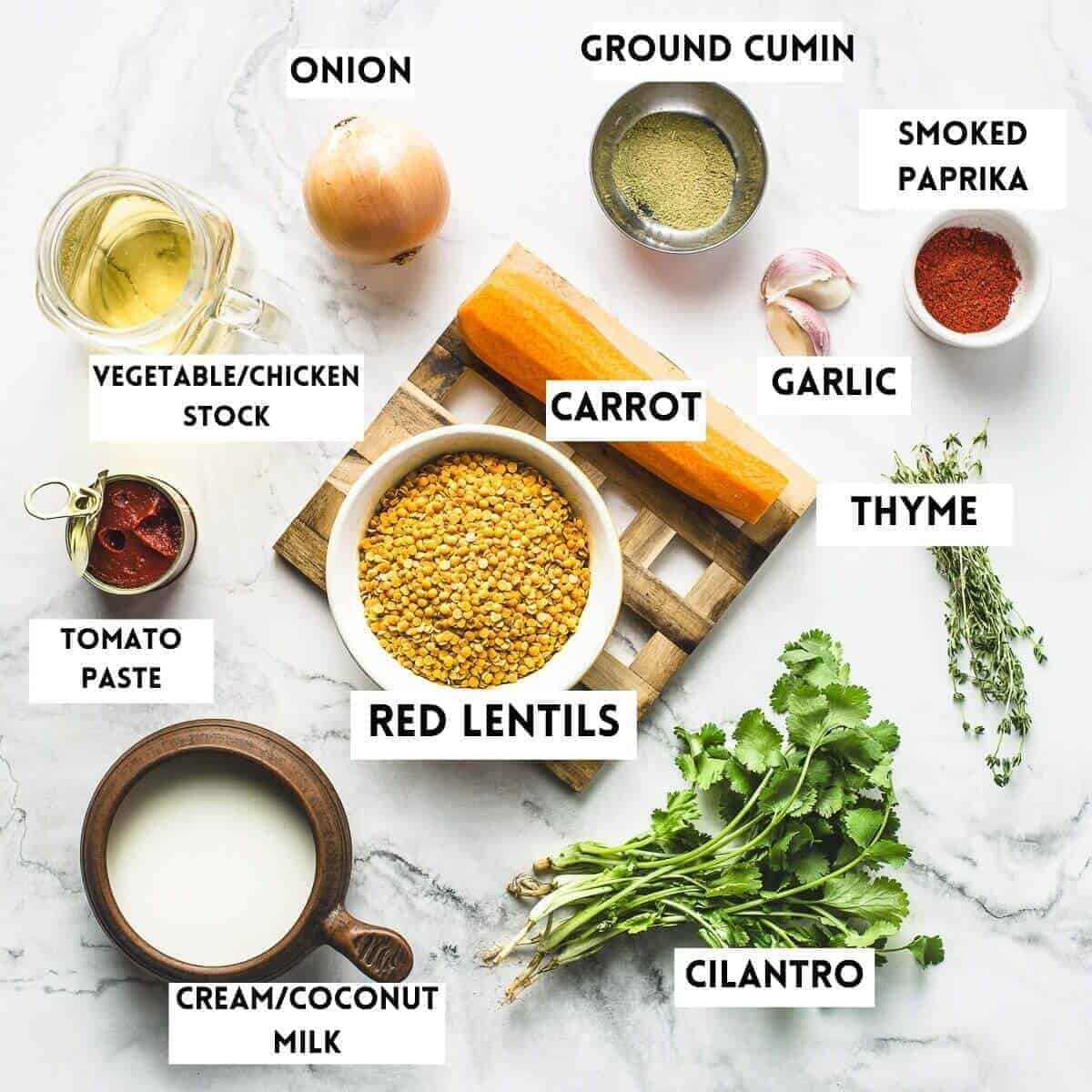 Picture of ingredients needed to cook red lentil soup. Carrot, onion, cilantro, thyme, cream, tomato paste, stock, garlic, spices