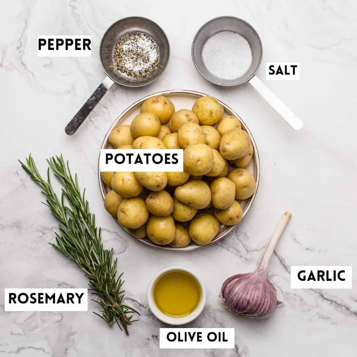 baby potatoes, rosemary, oil,garlic,salt,pepper on marble