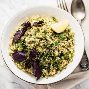 moroccan spiced couscous salad in a white bowl on marble background with purple basil and a wedge of lemon