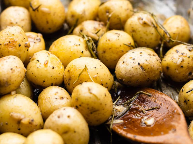 baked baby potatoes on oven tray with wooden spoon