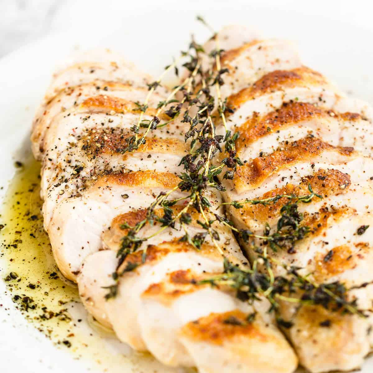 sliced oven roasted chicken breast with thyme butter on a white plate