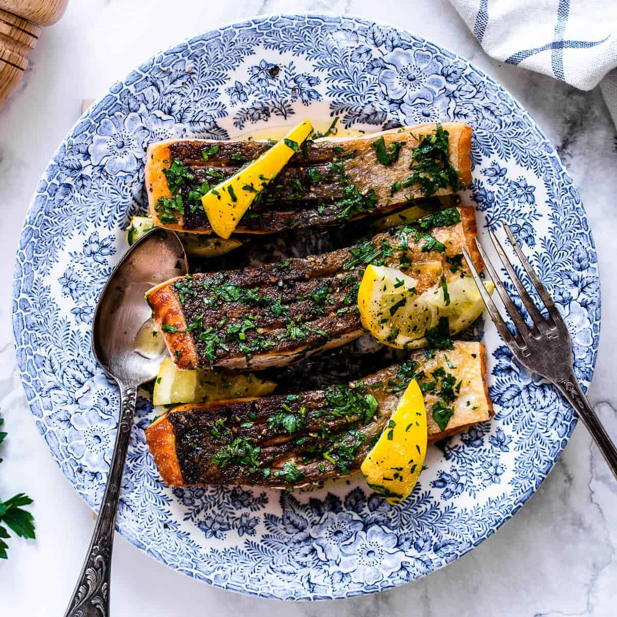 pan fried salmon fillet with crispy skin and lemon herb butter on a blue vintage plate.