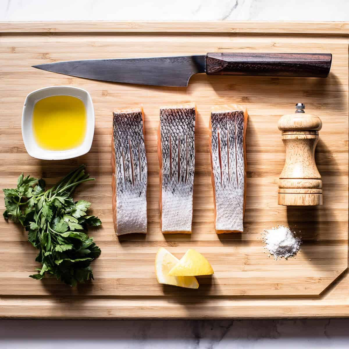 ingredients needed to pan fry salmon on a wooden board.