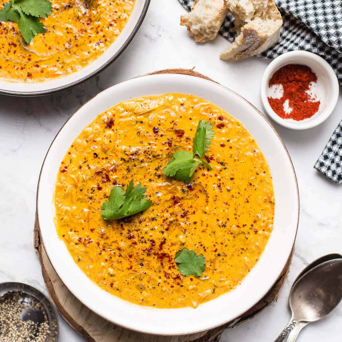 red lentil soup with cilantro in a white bowl