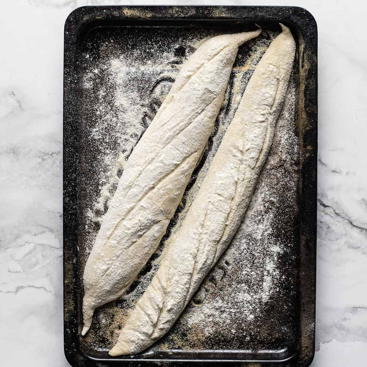 two raw baguettes slashed on a black oven tray