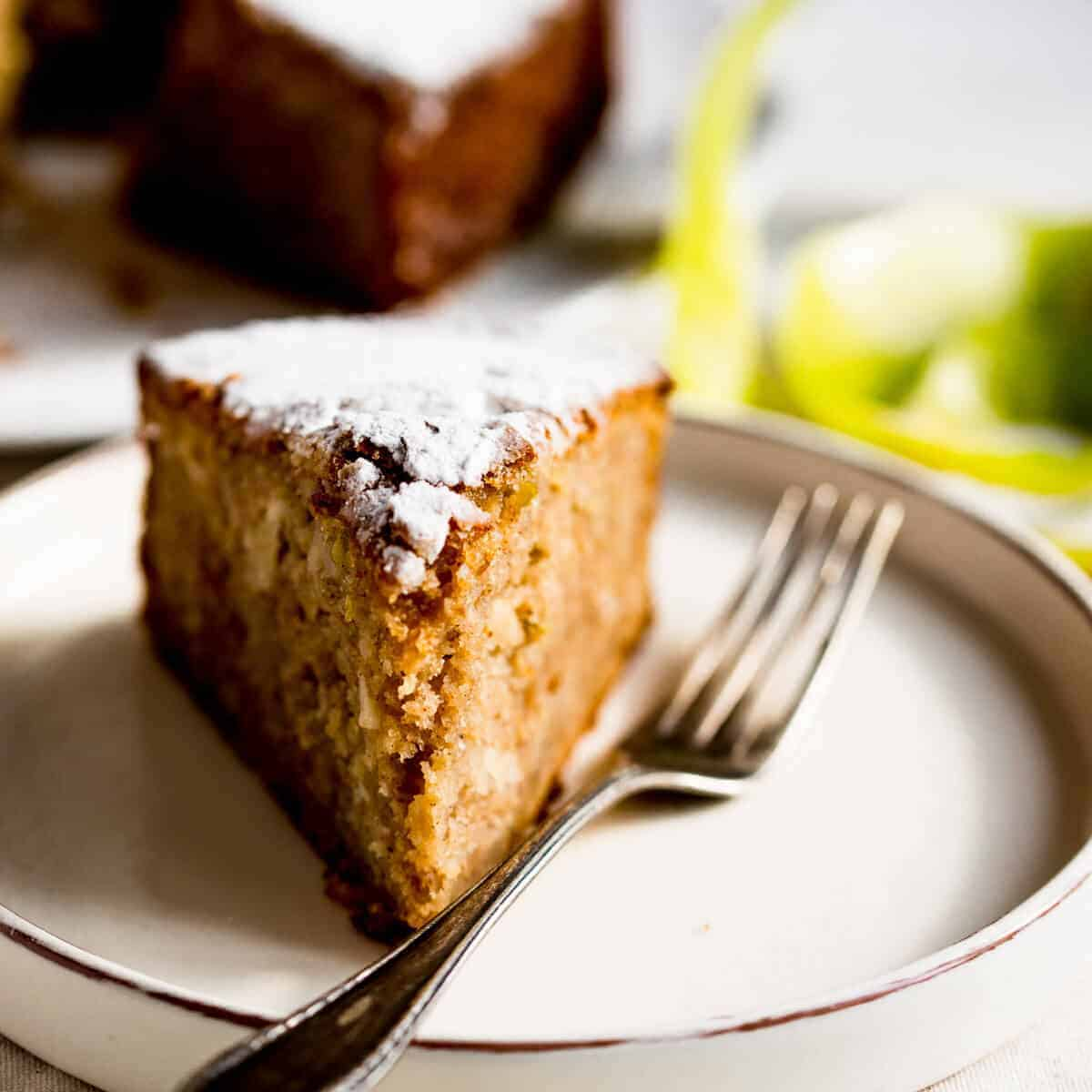 slice of spiced apple cake on a plate with vintage fork