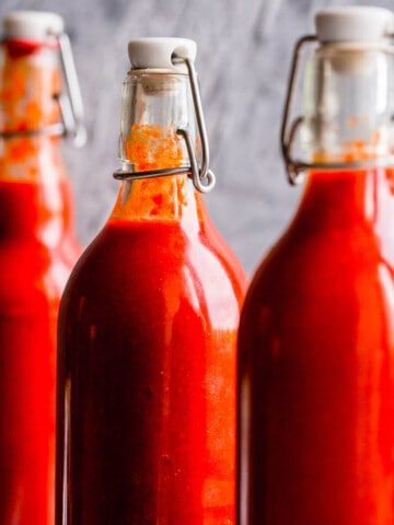 sriracha hot sauce in swing top bottles on grey background.