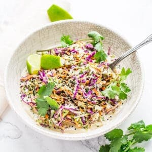 coleslaw with cilantro and lime in a white bowl on marble background