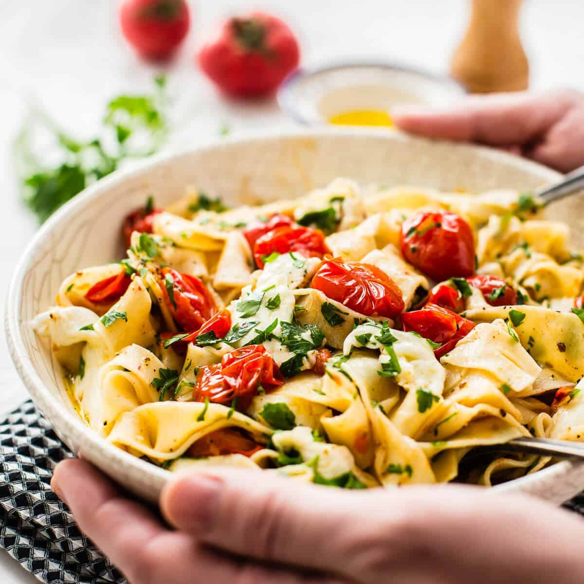 cherry tomato pasta in white bowl. Hands holding the bowl served on a black napkin with tomato, olive oil, pepper grinder and parsley in the background