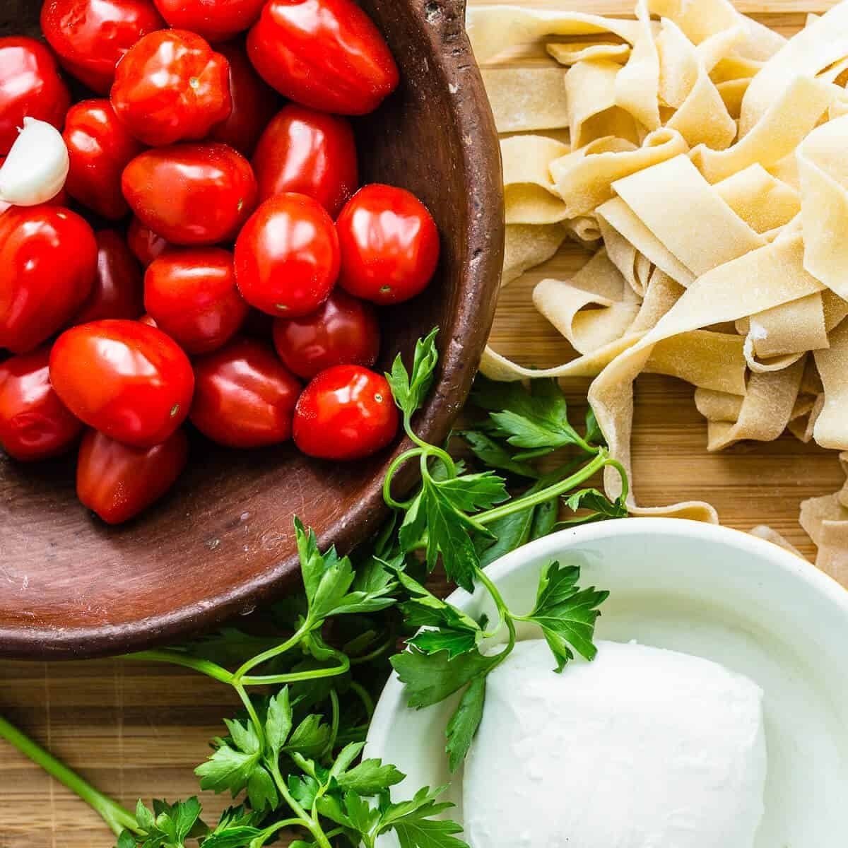 red cherry tomatoes in brown bowl on wooden chopping board with freshly made raw tagliatelle pasta, green parsley and fresh buffalo mozzarella ball in white bowl