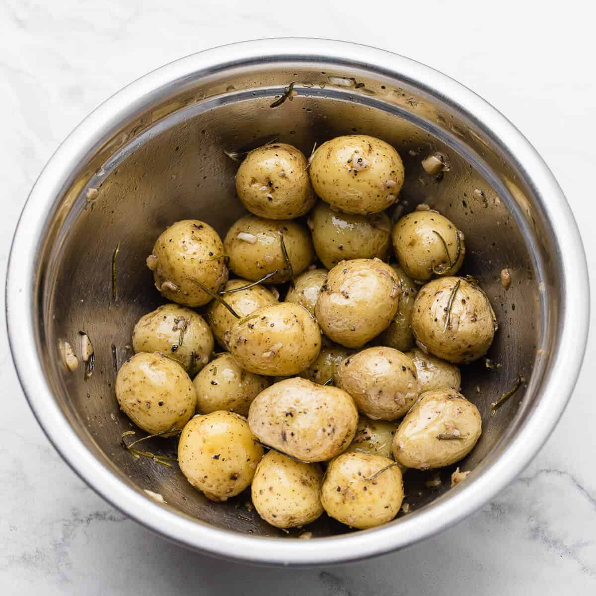 baked baby potatoes in stainless steel bowl on marble
