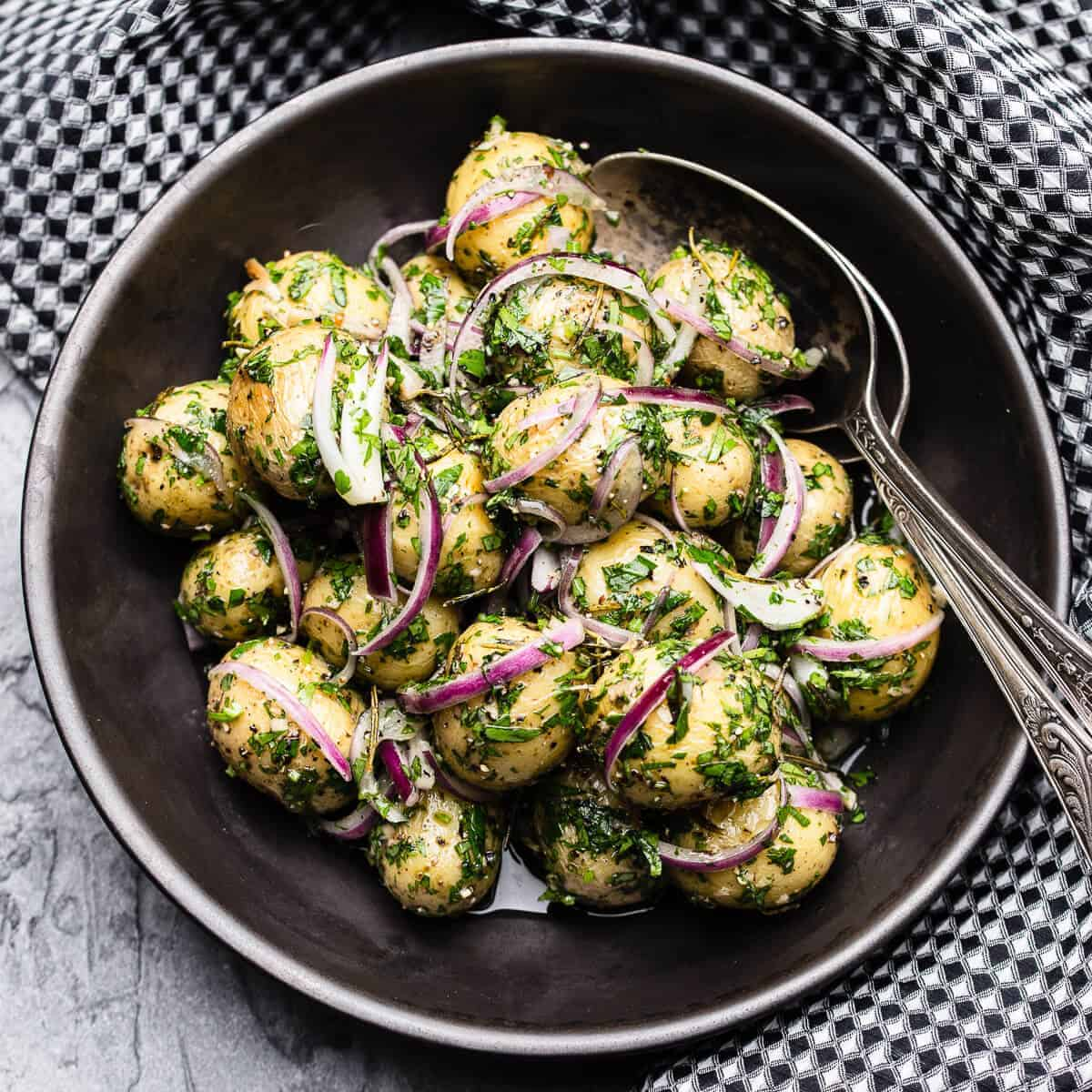 warm potato salad with red onion and parsley in a black bowl with black and white checkered napkin
